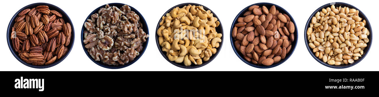 Close-up View from above of healthy Pecans, Walnuts, Cashews, Almonds and Peanuts. Closeup of different Nuts in a Bowl reflecting on white Background. - Stock Image