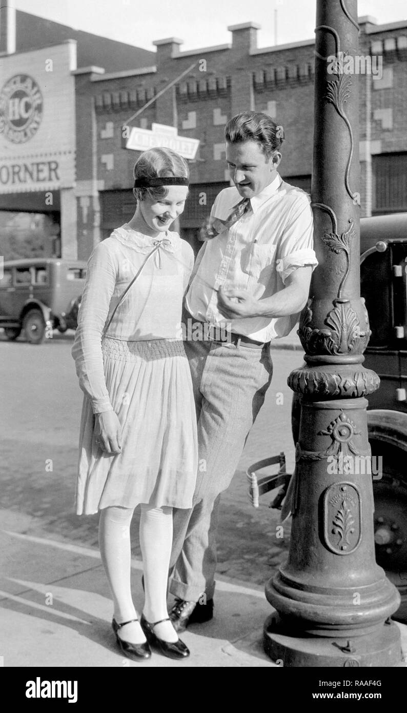 A man flirts with a younger woman on the street, ca. 1925. - Stock Image