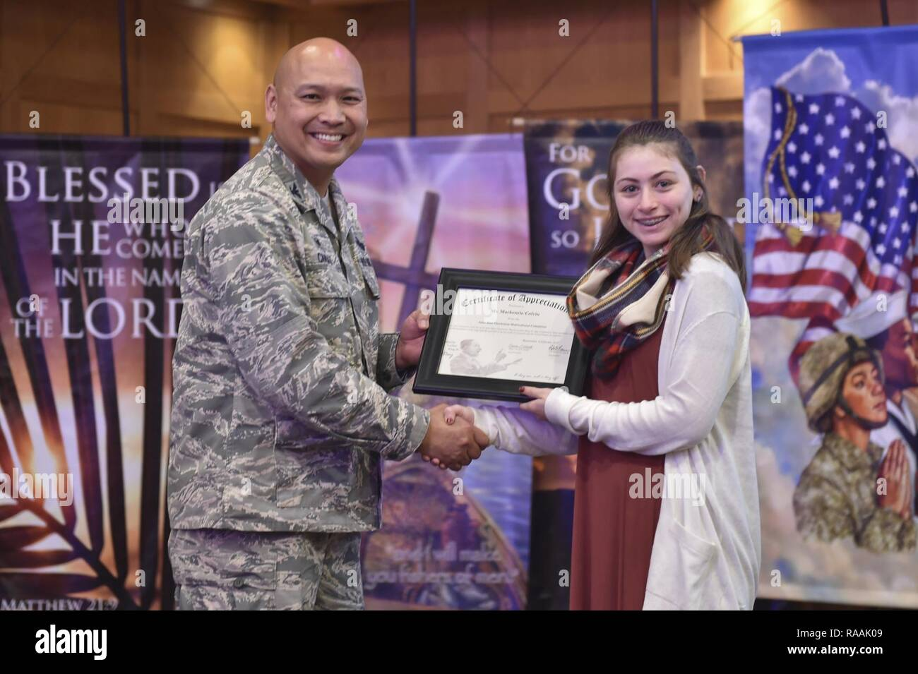 U.S. Air Force Col. Jimmy Canlas, 437 Airlift Wing commander, presents Mackenzie Colvin, a student from Gregg Middle School, with a certificate of appreciation during the Dr. Martin Luther King Jr. remembrance event at the Air Base Chapel Jan. 17, 2017 at Joint Base Charleston, South Carolina. Colvin recited a speech written by King during the ceremony. - Stock Image