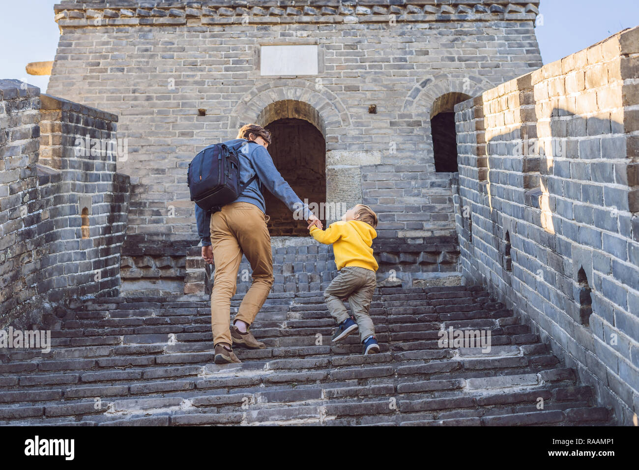 Happy cheerful joyful tourists dad and son at Great Wall of China having fun on travel smiling laughing and dancing during vacation trip in Asia. Chinese destination. Travel with children in China concept Stock Photo