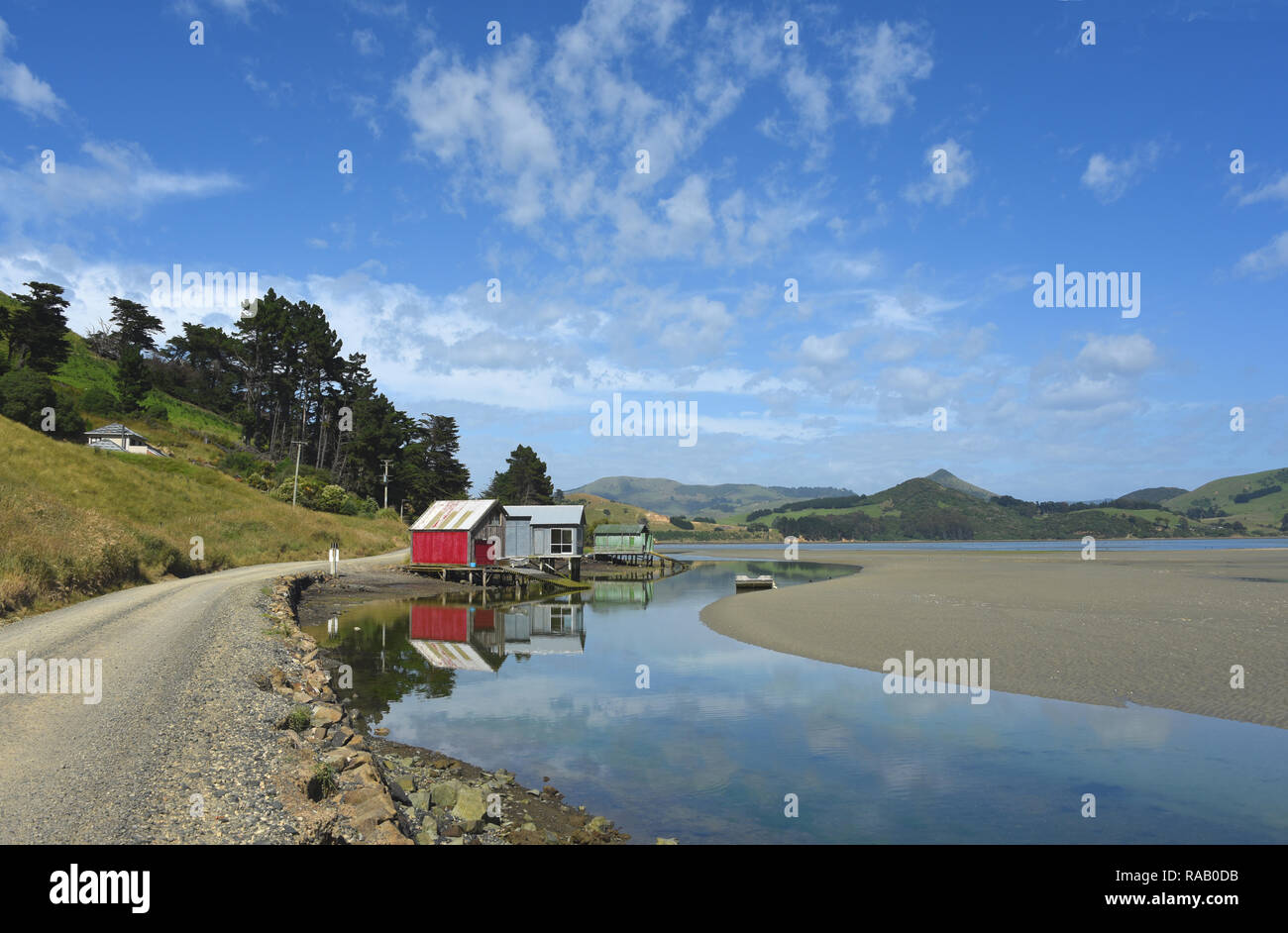 Amazing reflections of colorful ancient boat houses on the Otago peninsula of the South island of New Zealand. - Stock Image