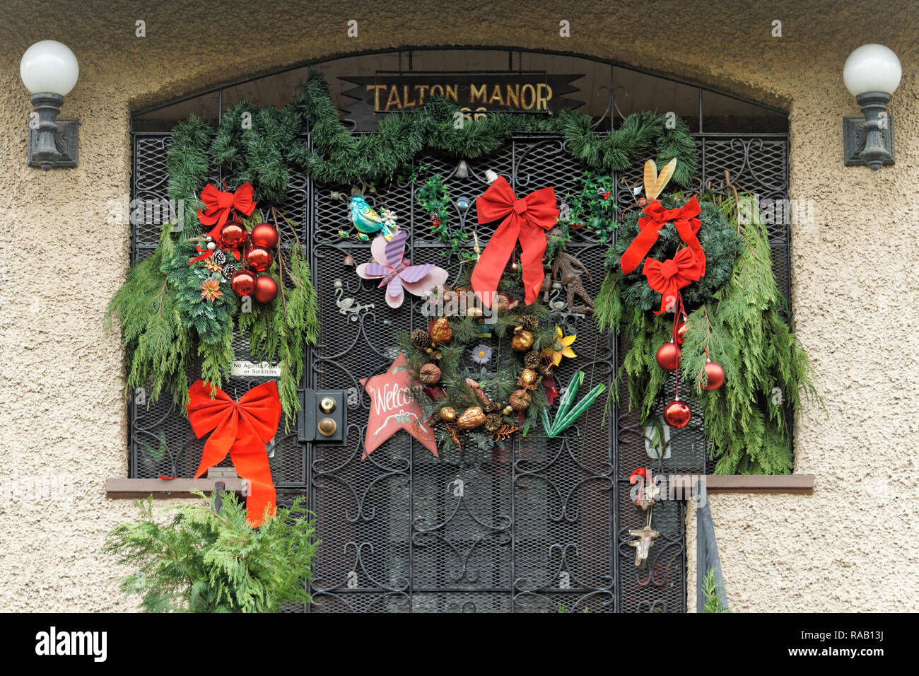 Variety Of Christmas Decorations Hanging From The Metal Front Door Gate Of  An Apartment Building