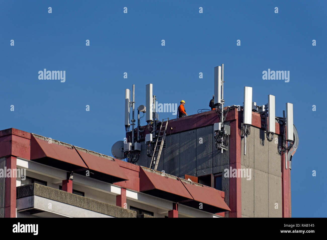 Cellphone antennas and a telecommunications workers on top of an apartment building in Vancouver, BC, Canada Stock Photo