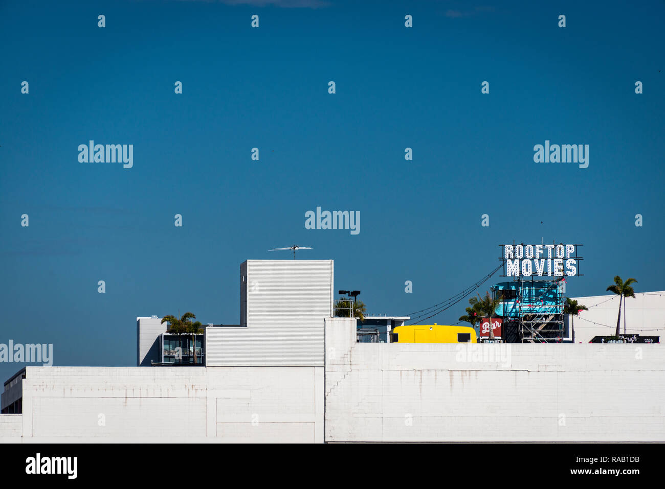 A sign for Rooftop Movies on a white concrete building against a vivid blue sky - Stock Image