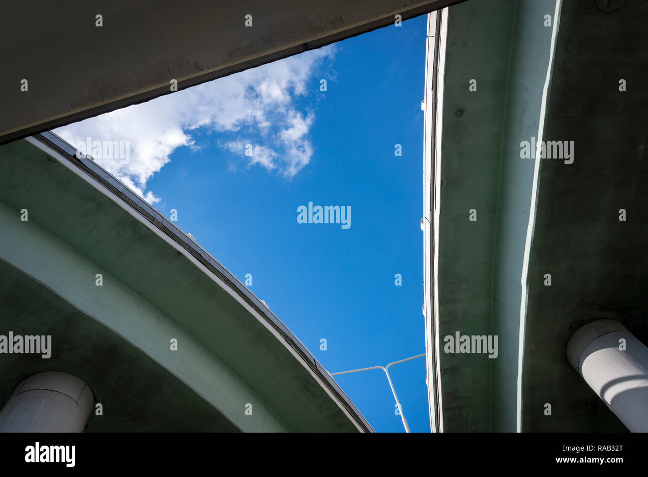 A triangular area of sky made by the intersecting of three concrete overpasses - Stock Image