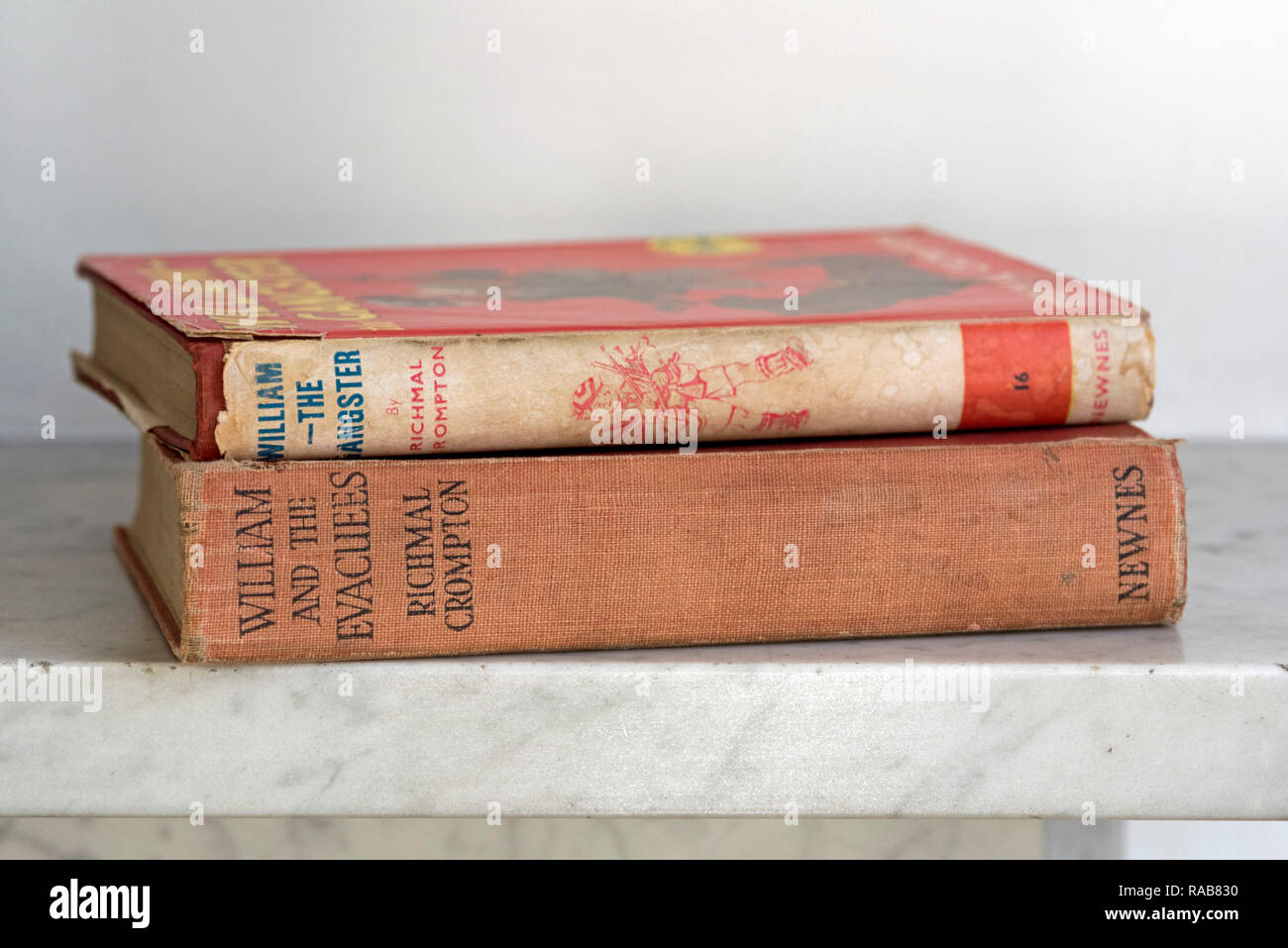 Two vintage Just William books: William the Gangster and William and the Evacuees by Richmal Crompton on grey marble mantlepiece. Editorial use only. - Stock Image