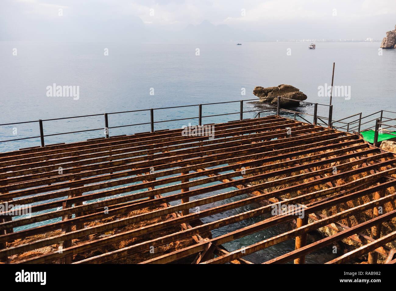 Finish of summer beach holidays season concept. Disassembled wooden pontoon at seashore. Preparations to winter cold season. Horizontal color photogra - Stock Image