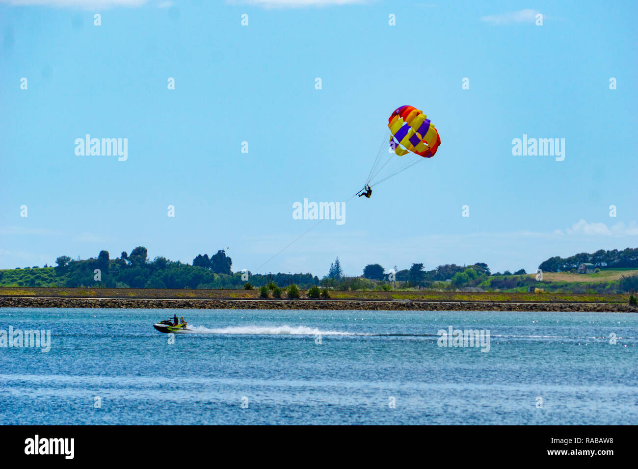 TAURANGA, NEW ZEALAND DECEMBER 22 2018; Summer fun being towed over the bay while hanging under a paraglider. - Stock Image