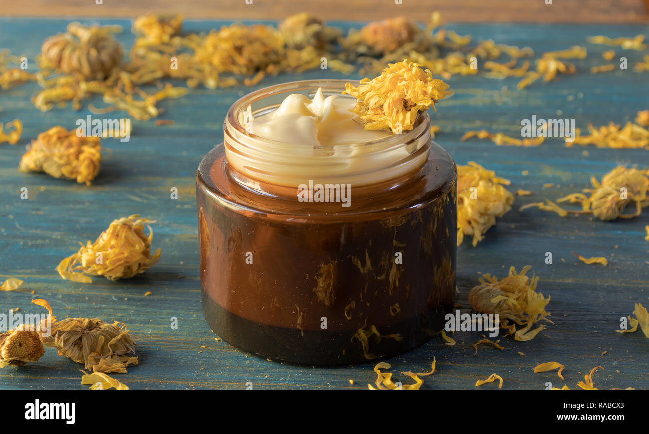 Facial cream of calendula, and beeswax, on a wooden background - Stock Image
