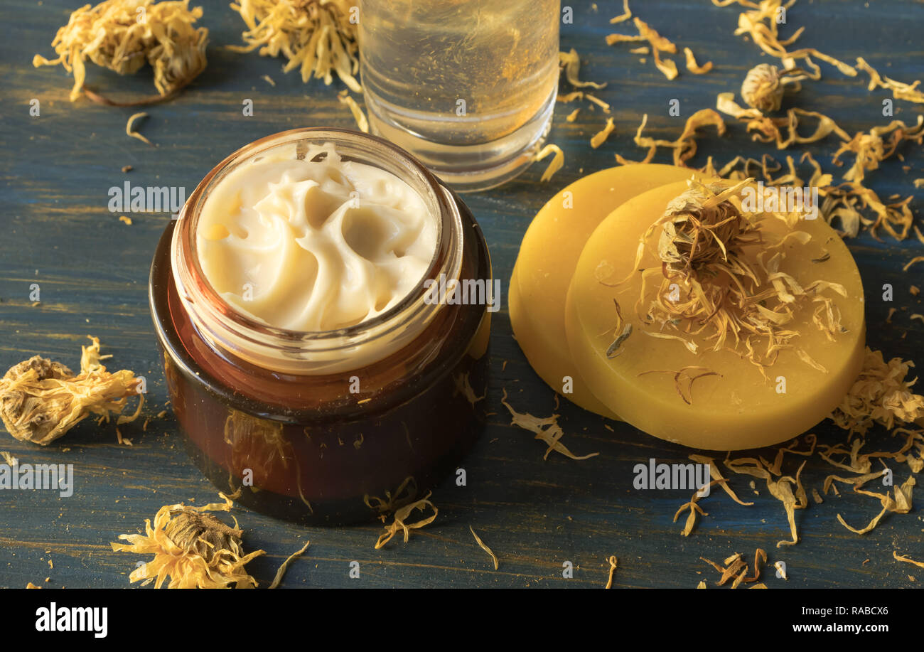 Facial cream of calendula and beeswax, on a blue wooden background - Stock Image