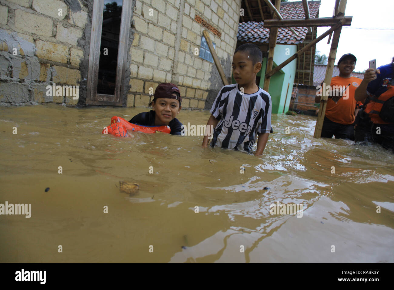 Children are seen playing inside the water during a flood. Dozens of residents were evacuated due to the flood disaster that hit village Rancamaya Cikobak RT 03/04, Rancamaya, Bogor City. This flood began to hit dozens of houses in Kampung Rancamaya Cikobak due to the flow of the Cisadane tributary, the Cimakaci River overflowing. Stock Photo
