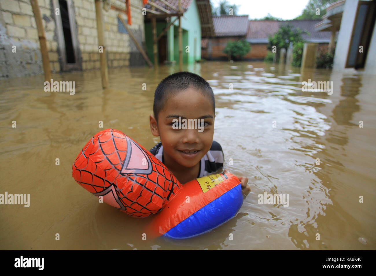 A child seen playing inside the water during a flood. Dozens of residents were evacuated due to the flood disaster that hit village Rancamaya Cikobak RT 03/04, Rancamaya, Bogor City. This flood began to hit dozens of houses in Kampung Rancamaya Cikobak due to the flow of the Cisadane tributary, the Cimakaci River overflowing. - Stock Image