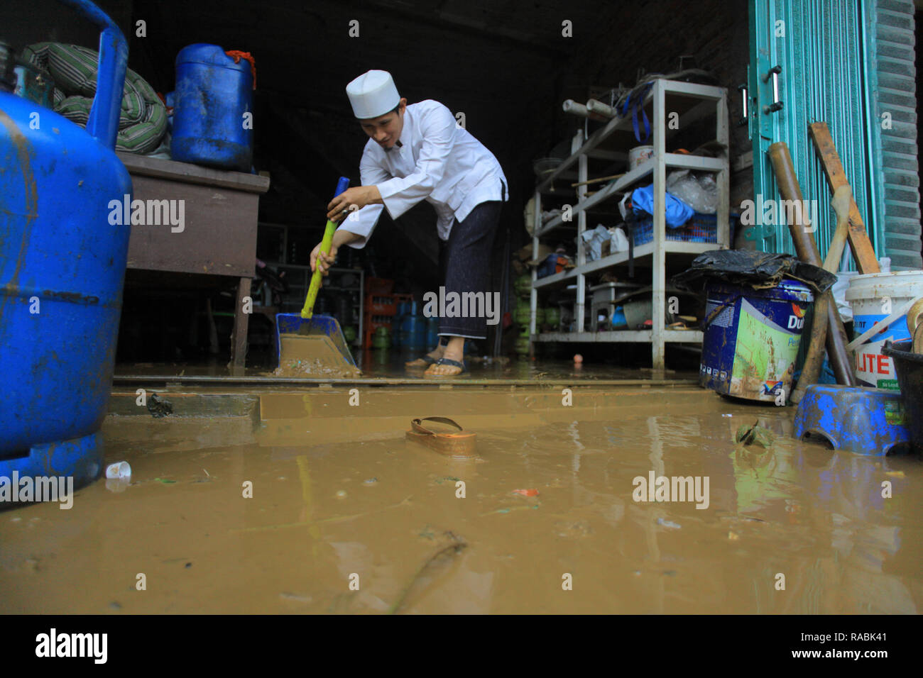 Resident seen cleaning his house during a flood. Dozens of residents were evacuated due to the flood disaster that hit village Rancamaya Cikobak RT 03/04, Rancamaya, Bogor City. This flood began to hit dozens of houses in Kampung Rancamaya Cikobak due to the flow of the Cisadane tributary, the Cimakaci River overflowing. - Stock Image