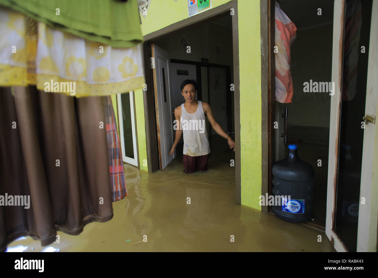Resident seen inside his house during a flood. Dozens of residents were evacuated due to the flood disaster that hit village Rancamaya Cikobak RT 03/04, Rancamaya, Bogor City. This flood began to hit dozens of houses in Kampung Rancamaya Cikobak due to the flow of the Cisadane tributary, the Cimakaci River overflowing. - Stock Image