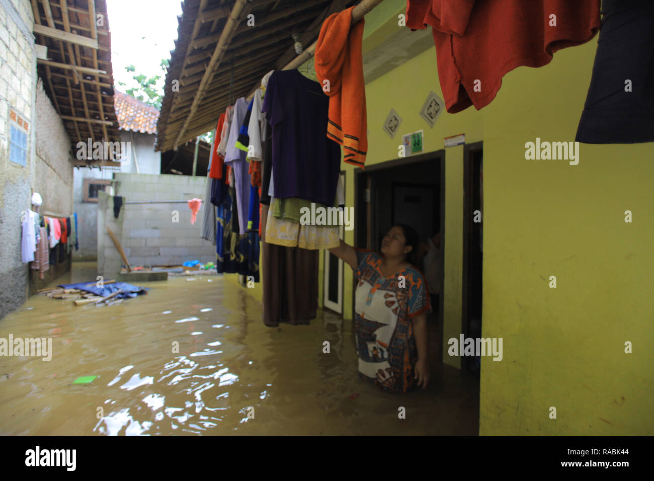 Resident seen cleaning her house during a flood. Dozens of residents were evacuated due to the flood disaster that hit village Rancamaya Cikobak RT 03/04, Rancamaya, Bogor City. This flood began to hit dozens of houses in Kampung Rancamaya Cikobak due to the flow of the Cisadane tributary, the Cimakaci River overflowing. - Stock Image