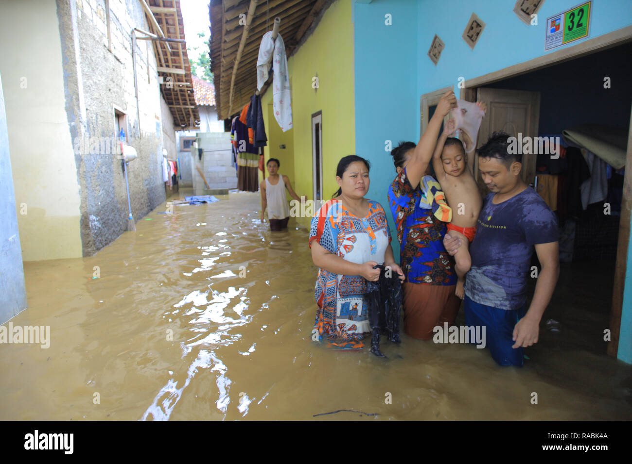 Bogor, West Java, Indonesia. 2nd Jan, 2019. Residents seen outside of their house during a flood. Dozens of residents were evacuated due to the flood disaster that hit village Rancamaya Cikobak RT 03/04, Rancamaya, Bogor City. This flood began to hit dozens of houses in Kampung Rancamaya Cikobak due to the flow of the Cisadane tributary, the Cimakaci River overflowing. Credit: Adriana Adinandra/SOPA Images/ZUMA Wire/Alamy Live News - Stock Image