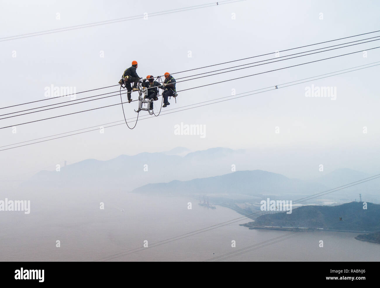 Zhoushan, China's Zhejiang Province. 3rd Jan, 2019. Staff members work on the cables at the site of the giant power supply pylons in Zhoushan, east China's Zhejiang Province, Jan. 3, 2019. The two 380-meter-tall pylons carry power cables between Zhoushan's Jintang and Cezi islands, a distance of 2,656 meters. The new pylon project is a part of a new ultra-high voltage power line project between cities of Zhoushan and Ningbo. Credit: Xu Yu/Xinhua/Alamy Live News - Stock Image