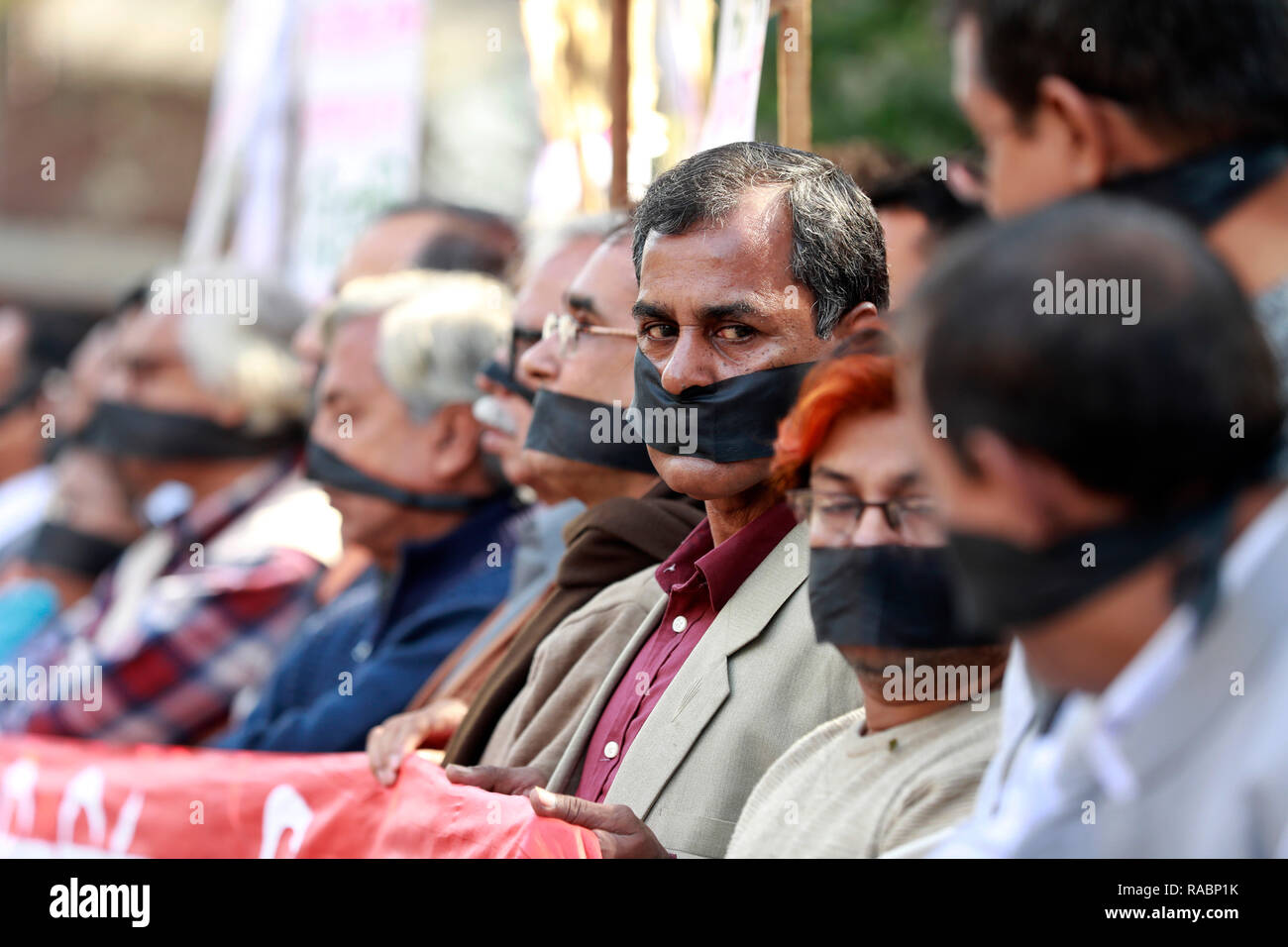 Dhaka, Bangladesh. 03rd Jan, 2019. Dhaka, Bangladesh - January 03, 2019: Bangladeshi left-wing activists organized by the Communist Party of Bangladesh wear black cloth over their mouths at a protest against the allegedly fraudulent victory of the ruling Awami League in the recent general election, in Dhaka on January 3, 2019. Credit: SK Hasan Ali/Alamy Live News - Stock Image