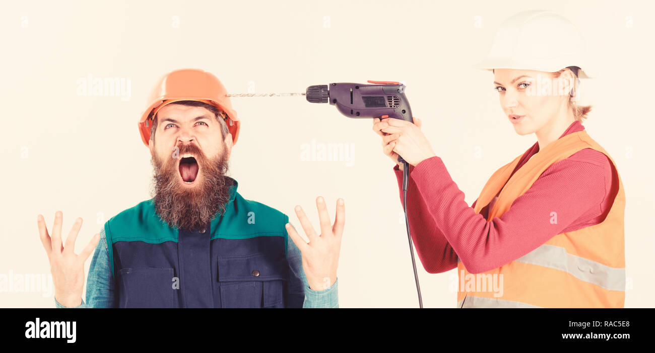 Husband annoyed by wife. Builder makes hole in male head. Marriage issues concept. Woman drills head of man, white background. Man in helmet with shouting face fed up of his wife drilling him. Stock Photo