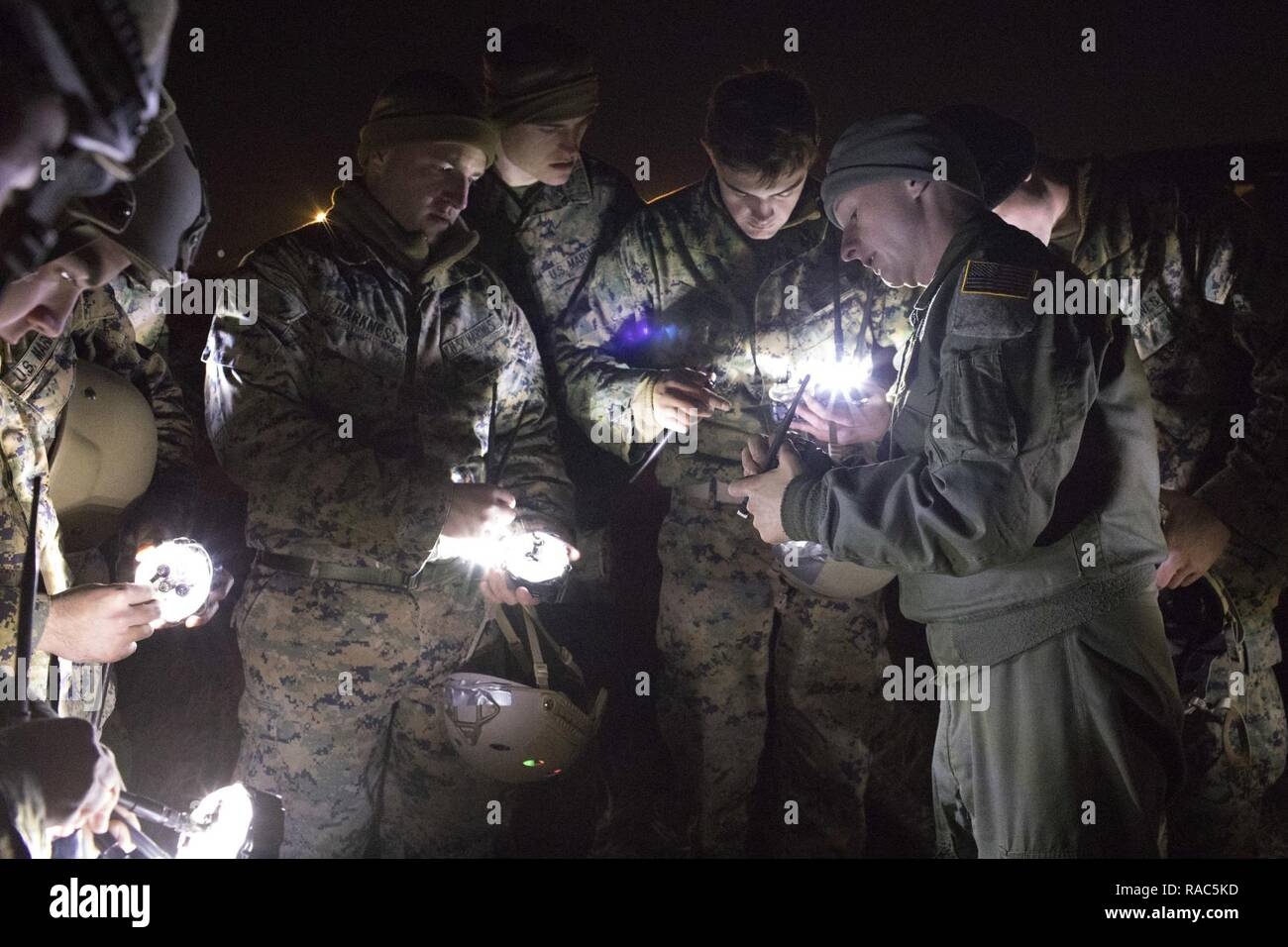 1st Lt. John Adams, right,  36th Airlift Squadron C-130 Hercules navigator, shows Marines from the 3rd Reconnaissance Battalion, 3rd Marine Division, III Marine Expeditionary Force how to operate drop zone indicator lights at Yokota Air Base, Japan, Jan. 11, 2017, during Jump week. III MEF Marines conducted weeklong jump training from a U.S. Air Force C-130H, assigned to the 36 AS. The training not only allowed the Marines to practice jumping, but it also allowed the Yokota aircrews to practice flight tactics and time-package drops. Stock Photo