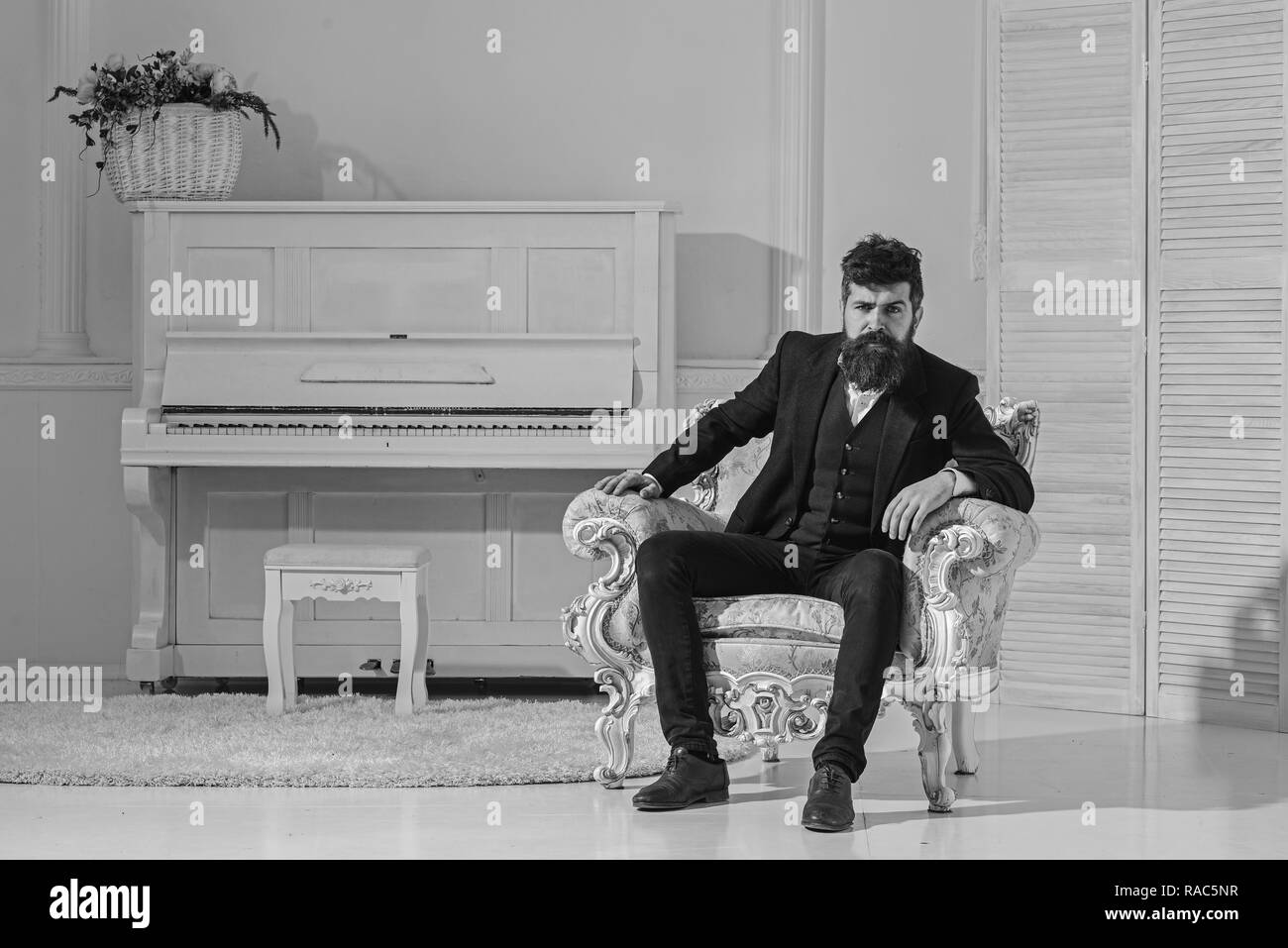 Macho attractive and elegant on serious, thoughtful face sitting on old fashioned armchair. Wealth and richness concept. Man with beard and mustache wearing classic suit, stylish fashionable outfit. - Stock Image