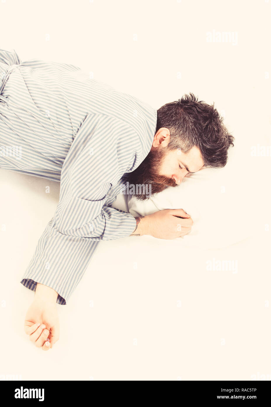Man with relaxed face, lay on pillow, top view. Hipster with beard fall asleep. Fast asleep concept. Hipster drowsy, exhausted, copy space. Man with beard in deep sleep, white background. - Stock Image