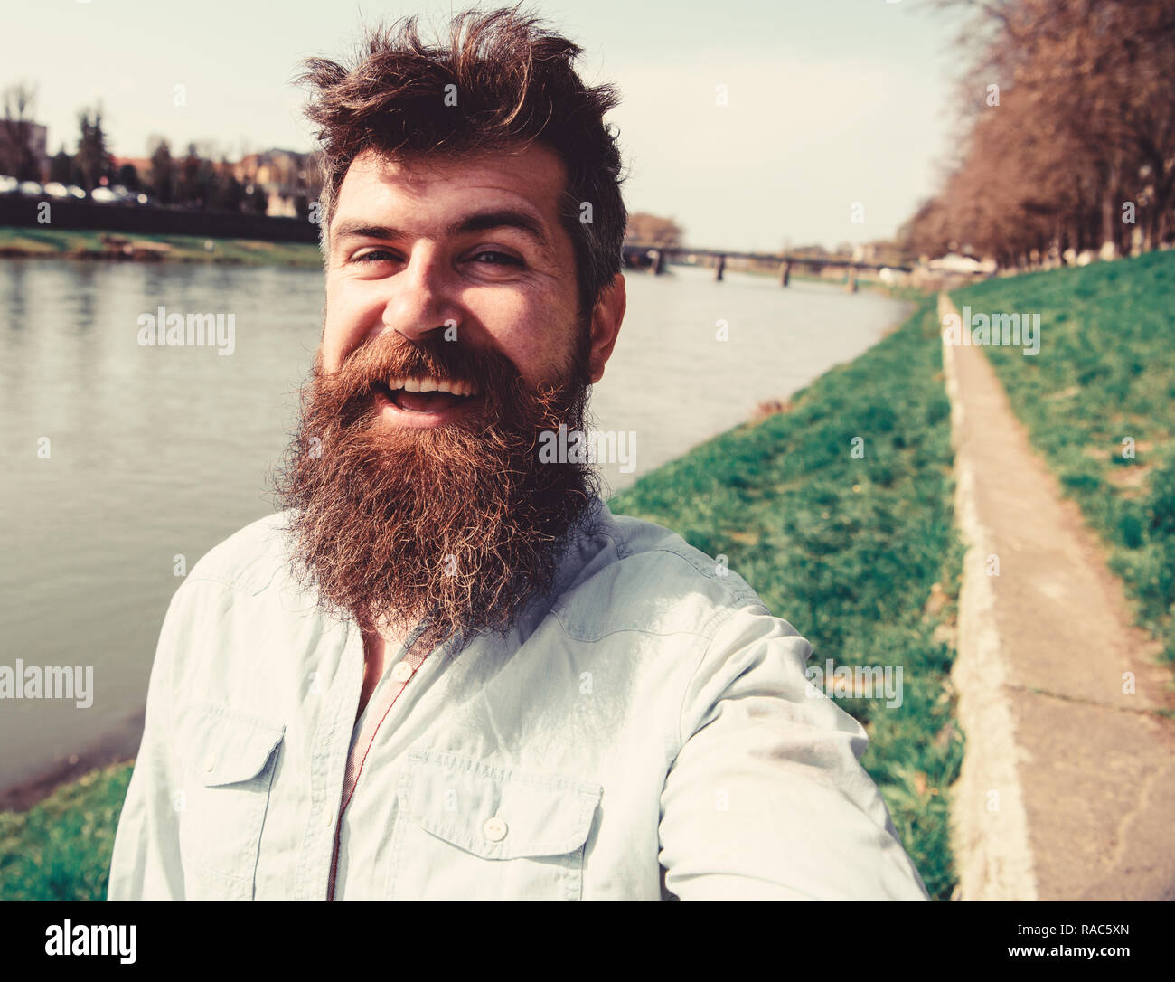 Man, tourist with beard and mustache on cheerful, smiling face, riverside background. Selfie photo concept. Hipster, tourist with tousled hair and long beard looking at camera, taking selfie photo. - Stock Image