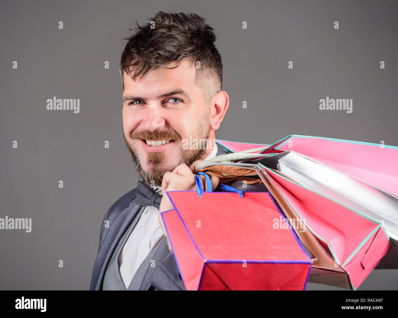 Man bearded elegant businessman carry shopping bags on grey background. Make shopping more joyful. Elite boutique. Enjoy shopping profitable deals black friday. Shopping with discount enjoy purchase. - Stock Image