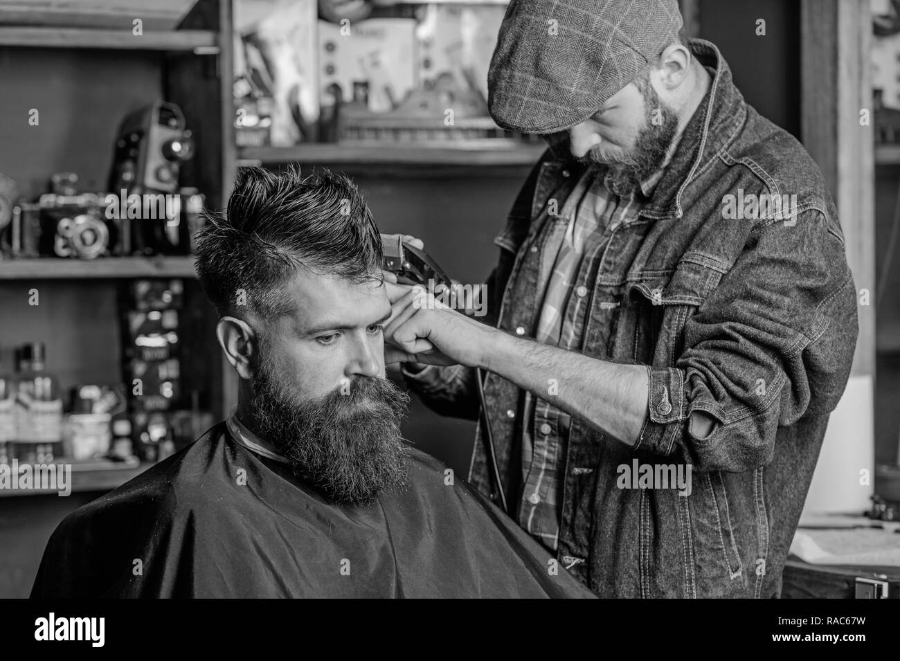 Hipster lifestyle concept. Hipster client getting haircut. Barber with hair clipper work on hairstyle for bearded hipster, barbershop background. Barber with clipper trimming hair on temple of client. - Stock Image