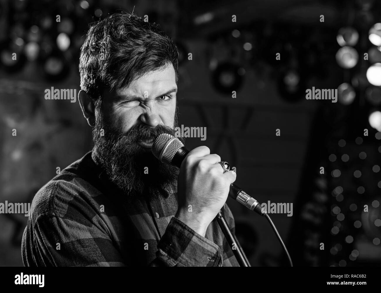 Musician with beard and mustache singing song in karaoke. Rock star concept. Man with enthusiastic face holds microphone, singing song, karaoke club background. Guy likes to sing in aggressive manner. - Stock Image