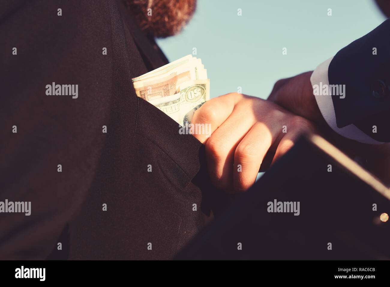 Man dressed in black suit holds folder takes bribe. Constructors make deal. Money, business and corruption concept. Manager puts money into pocket on blue sky background, close up. - Stock Image