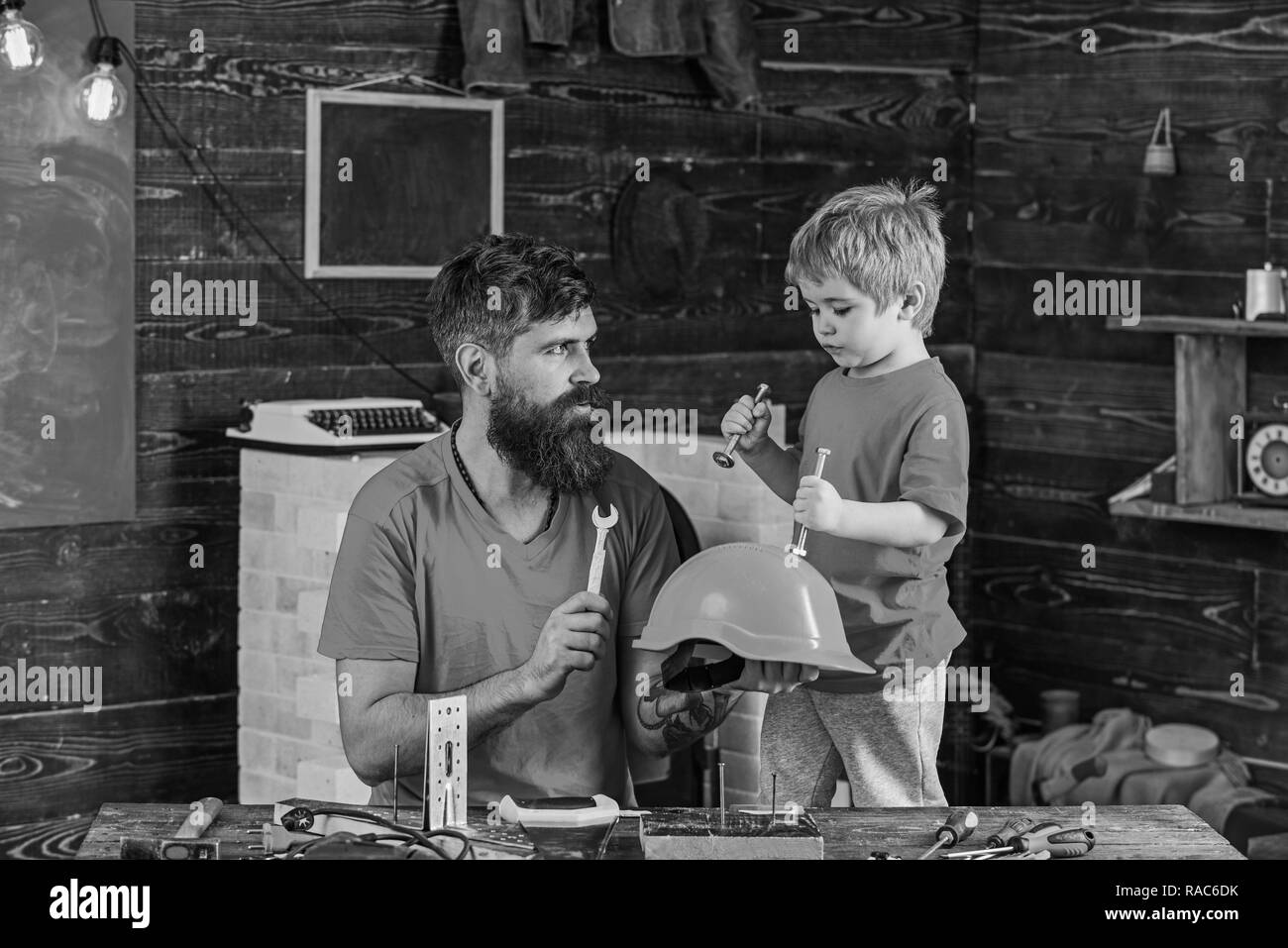 Safety and protection concept. Father, parent with beard holds helmet teaching son safety in school workshop. Boy, child cheerful holds bolts or screws, having fun while handcrafting with dad. - Stock Image