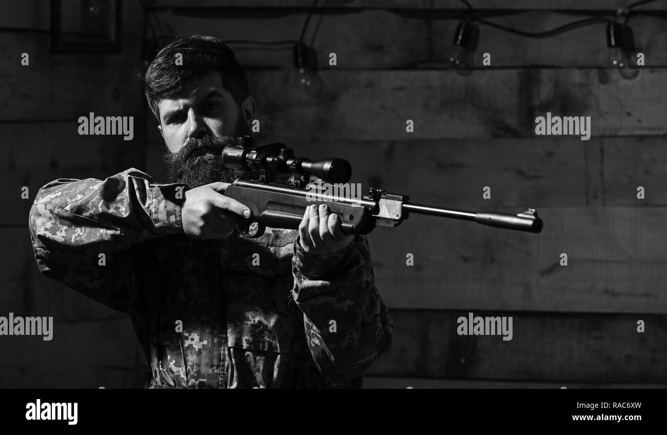 Man with beard wears camouflage clothing, wooden interior background. Hunter, brutal hipster with gun aiming before hunting, copy space. Huntsman concept. Macho on strict face at gamekeepers house. - Stock Image