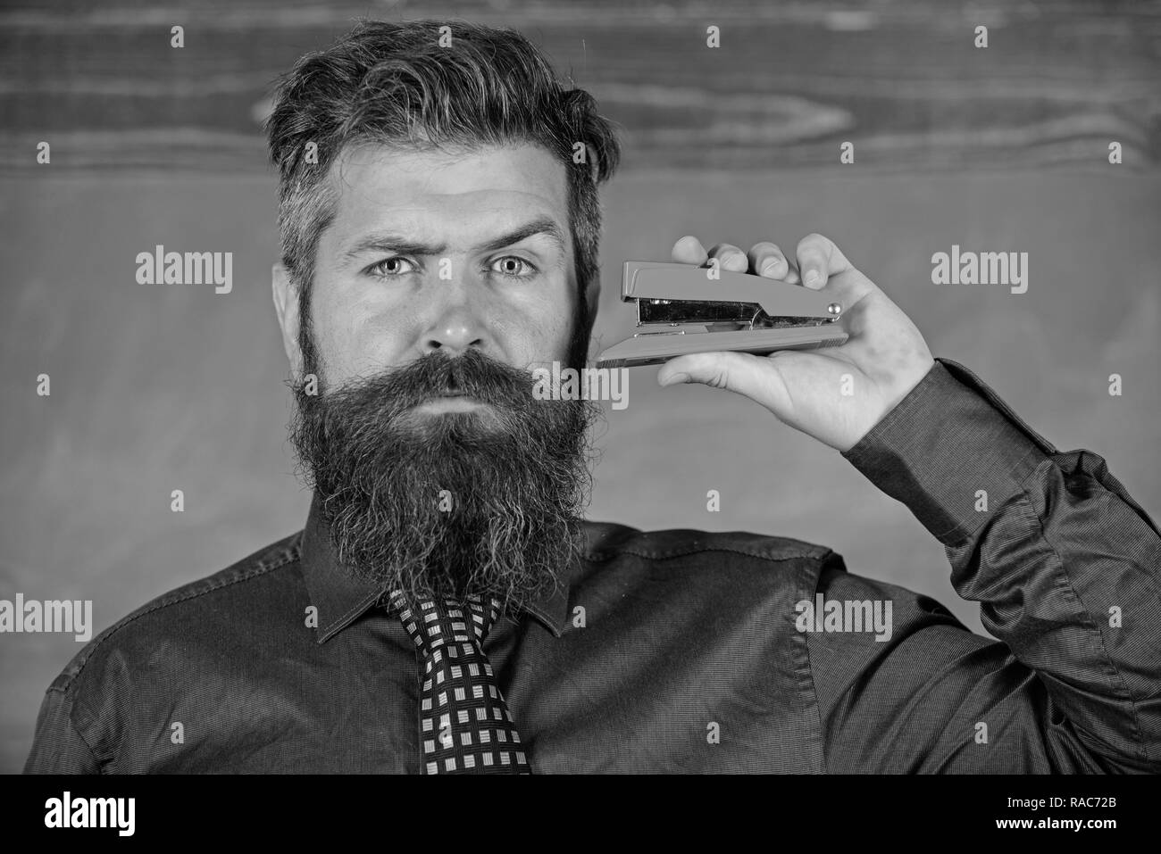 Teaching memorization techniques. Hipster teacher formal wear with neck tie holds stapler. Back to school and studying. Teacher bearded man with pink stapler chalkboard background. Pin it on mind. - Stock Image