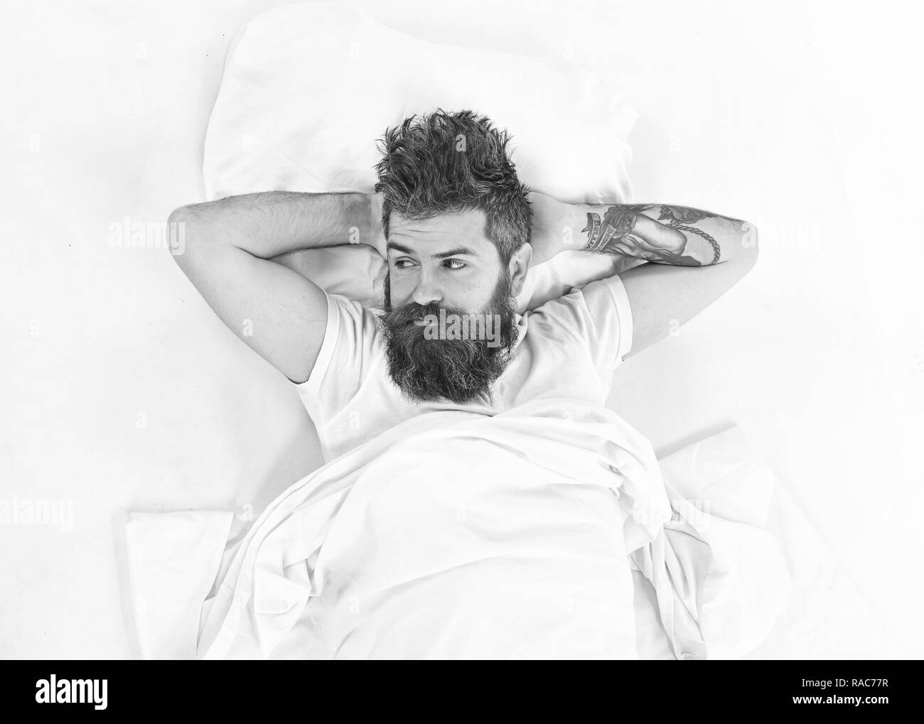 Man with pensive face wake up, lay on bed, put hands behind head, top view. Hipster with beard, mustache and messy hair relaxing. Hangover morning concept. Man relax and having rest, white background. - Stock Image