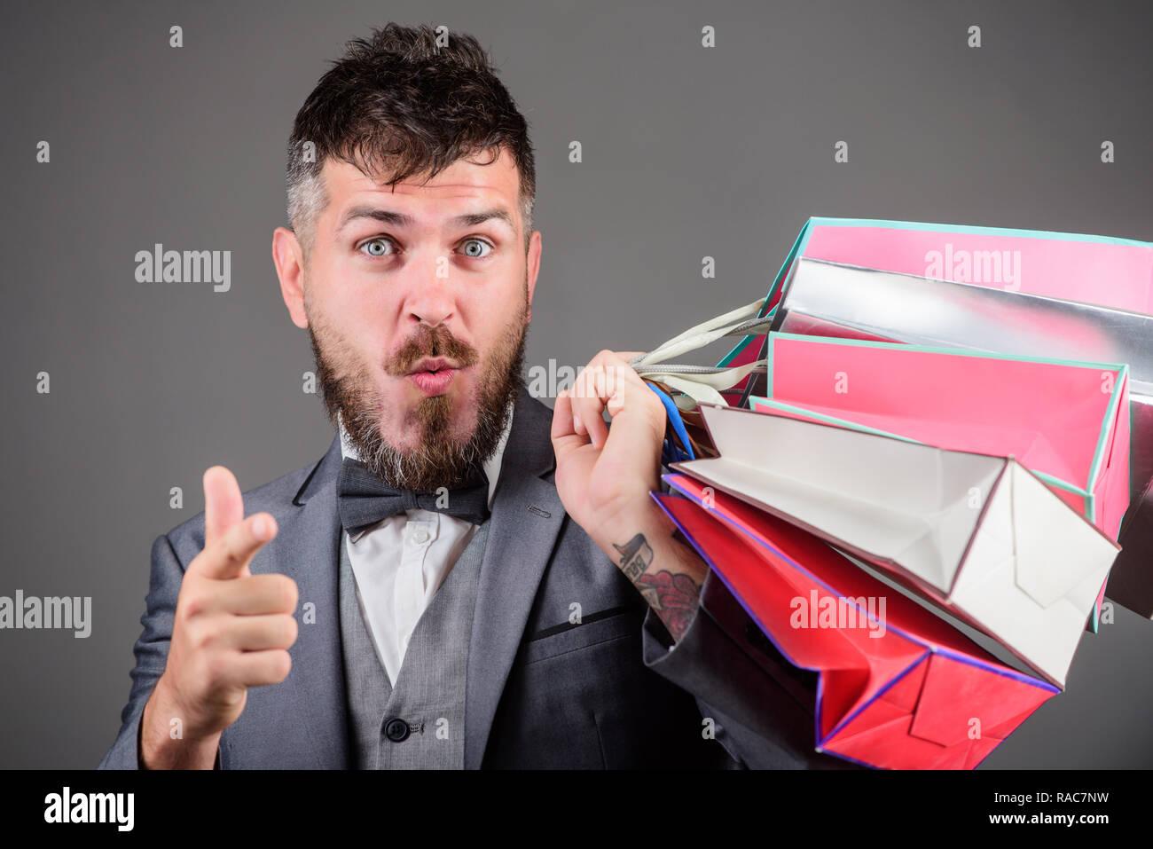 Elite boutique. Make shopping more joyful. Man bearded elegant businessman carry shopping bags on grey background. Enjoy shopping profitable deals black friday. Shopping with discount enjoy purchase. - Stock Image