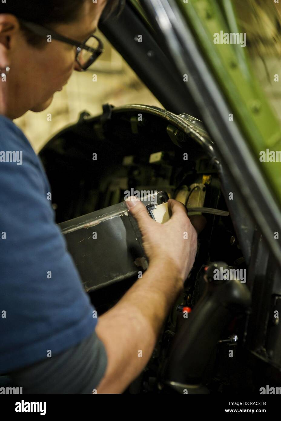 Kim Smith, 54th Helicopter Squadron UH-1N Iroquois mechanic, installs the attitude director indicator into a UH-1N Iroquois at Minot Air Force Base, N.D., Jan. 18, 2017. The ADI, aka gyro horizon, is an instrument that states the orientation of the helicopter to the horizon. - Stock Image