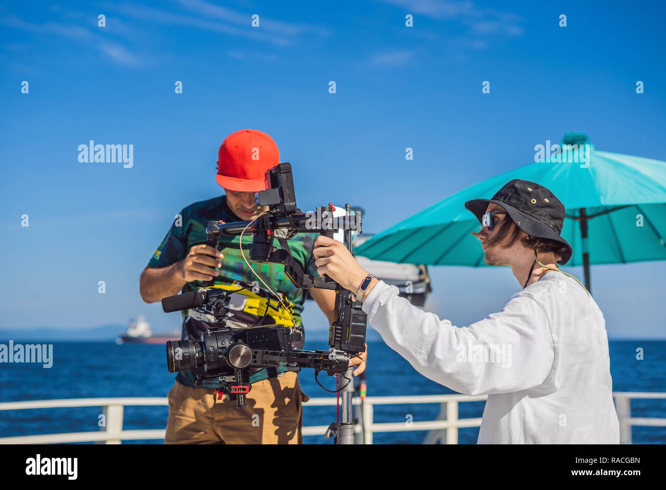 Steadicam operator and his assistant prepare camera and 3-axis stabilizer-gimbal for a commercial shoot - Stock Image