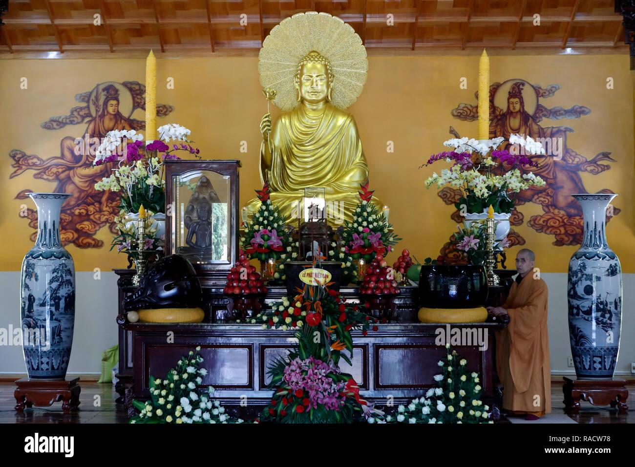 Main altar with Buddha statue and monk, Truc Lam Buddhist temple, Dalat, Vietnam, Indochina, Southeast Asia, Asia Stock Photo