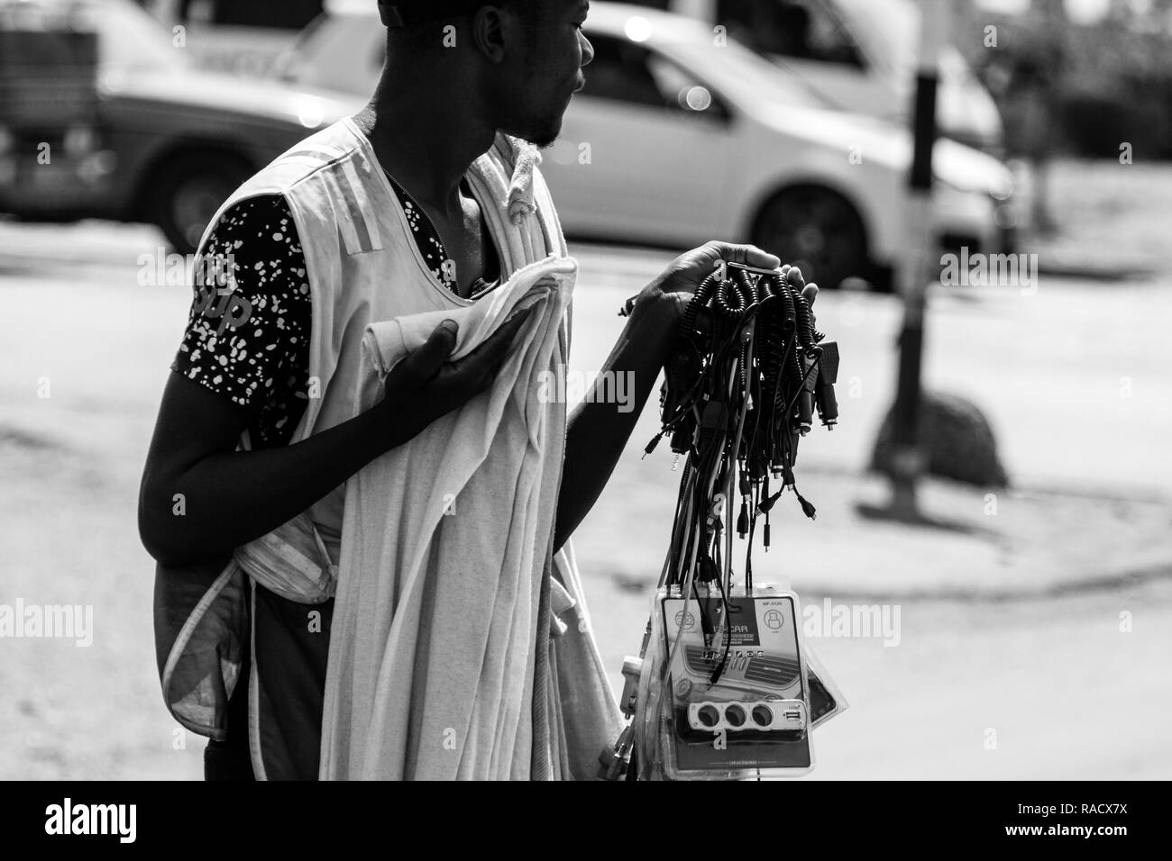 Harare, Zimbabwe - 23 Sep 2018: Young Zimbabwe street vendors sells his imported electronic wares at a traffic light due to unemployment. - Stock Image