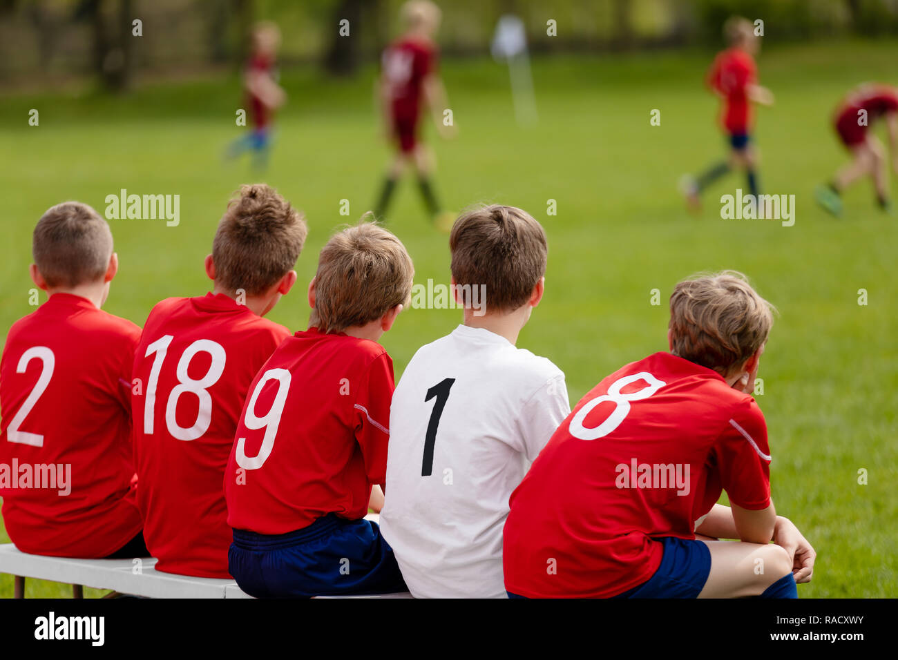 Kids Football Team. Children Football Academy. Substitute Soccer Players Sitting on Bench. Young Boys Playing European Football Game. Soccer Tournamen - Stock Image