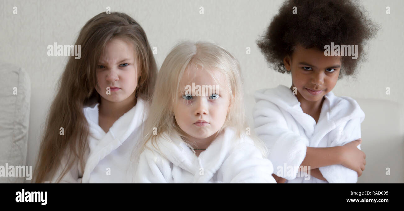 Three little girls of different nationalities are offended by their parents. - Stock Image