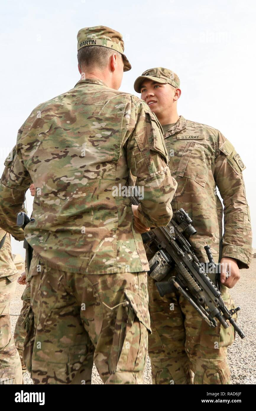 Maj. Gen. Joseph M. Martin, commanding general of the Combined Joint Forces Land Component Command-Operation Inherent Resolve, Iraq, and the 1st Infantry Division, congratulates Spc. Michael E. Mijares, an infantryman assigned to the 1st Squadron, 73rd Cavalry Regiment, 2nd Brigade Combat Team, 82nd Airborne Division, after the Paratrooper's three-year reenlistment at Qayyarah West, Iraq, Jan. 26, 2017. Deployed in support of Operation Inherent Resolve, the 2nd BCT, 82nd Abn. Div. enables their Iraqi Security Force partners through the advise and assist mission, contributing planning, intellig - Stock Image
