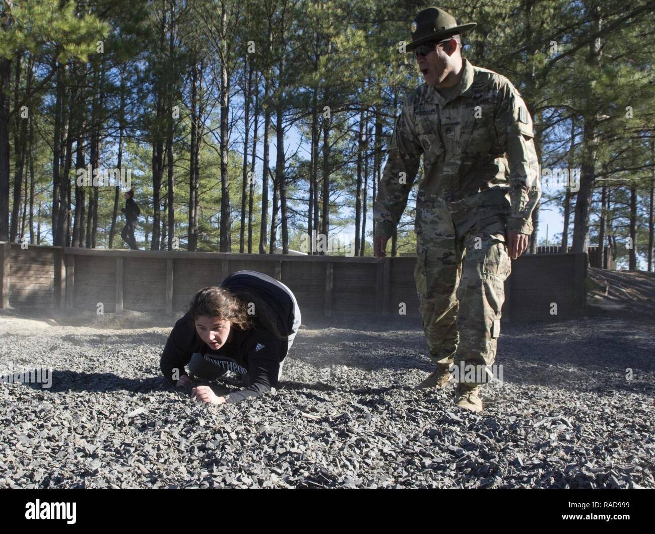 Alaina Girani, a junior goalie, and Wirtz, Va. native, on the Winthrop University Women's Lacrosse Team, is motivated to crawl to the end of Fit to Win 2 by Staff Sgt. Eric M. Driscoll, a drill sergeant with Alpha Company, 1st Battalion, 13th Infantry Regiment, during a team building exercise on Fort Jackson Jan. 28. - Stock Image