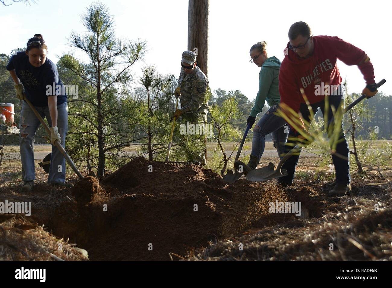 Team Shaw members shovel dirt into a defensive fighting position hole at Shaw Air Force Base, S.C., Feb. 1, 2017. The DFPs were built approximately 15 years ago for training exercises, but are no longer used. - Stock Image