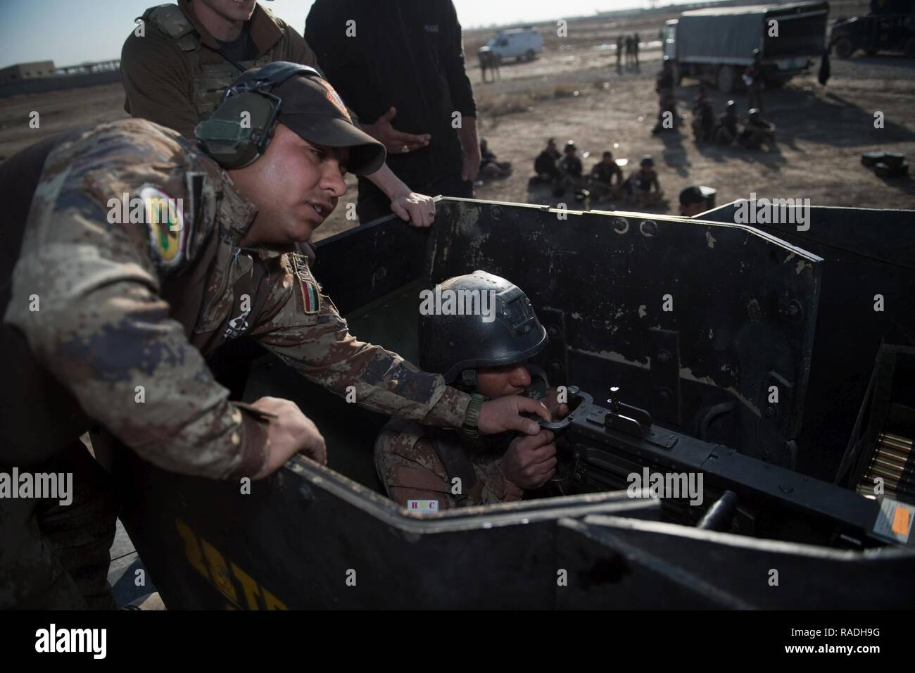 An Iraqi Counter-Terrorism Service instructor corrects a trainee operating the .50 caliber machine gun during live weapons training near Baghdad, Iraq, Jan. 31, 2017. ICTS is Iraq's elite counter-terrorism force and has proven to be an effective fighting force against ISIL. This training is part of the overall Combined Joint Task Force – Operation Inherent Resolve building partner capacity mission to increase the capacity of partnered forces fighting ISIL. CJTF-OIR is the global Coalition to defeat ISIL in Iraq and Syria. - Stock Image
