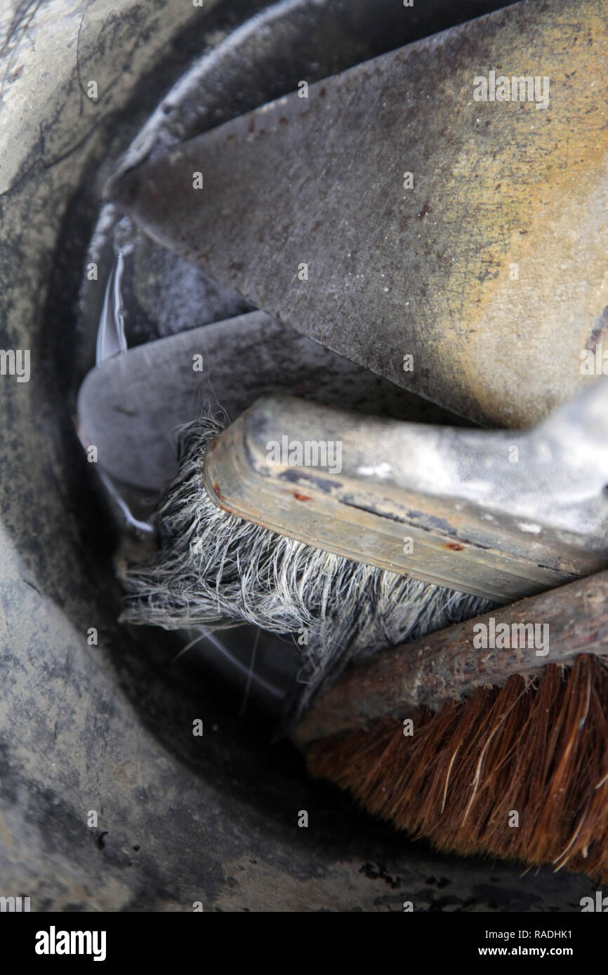 Close up of bucket with builder's trowel and brushes with out of focus - Stock Image