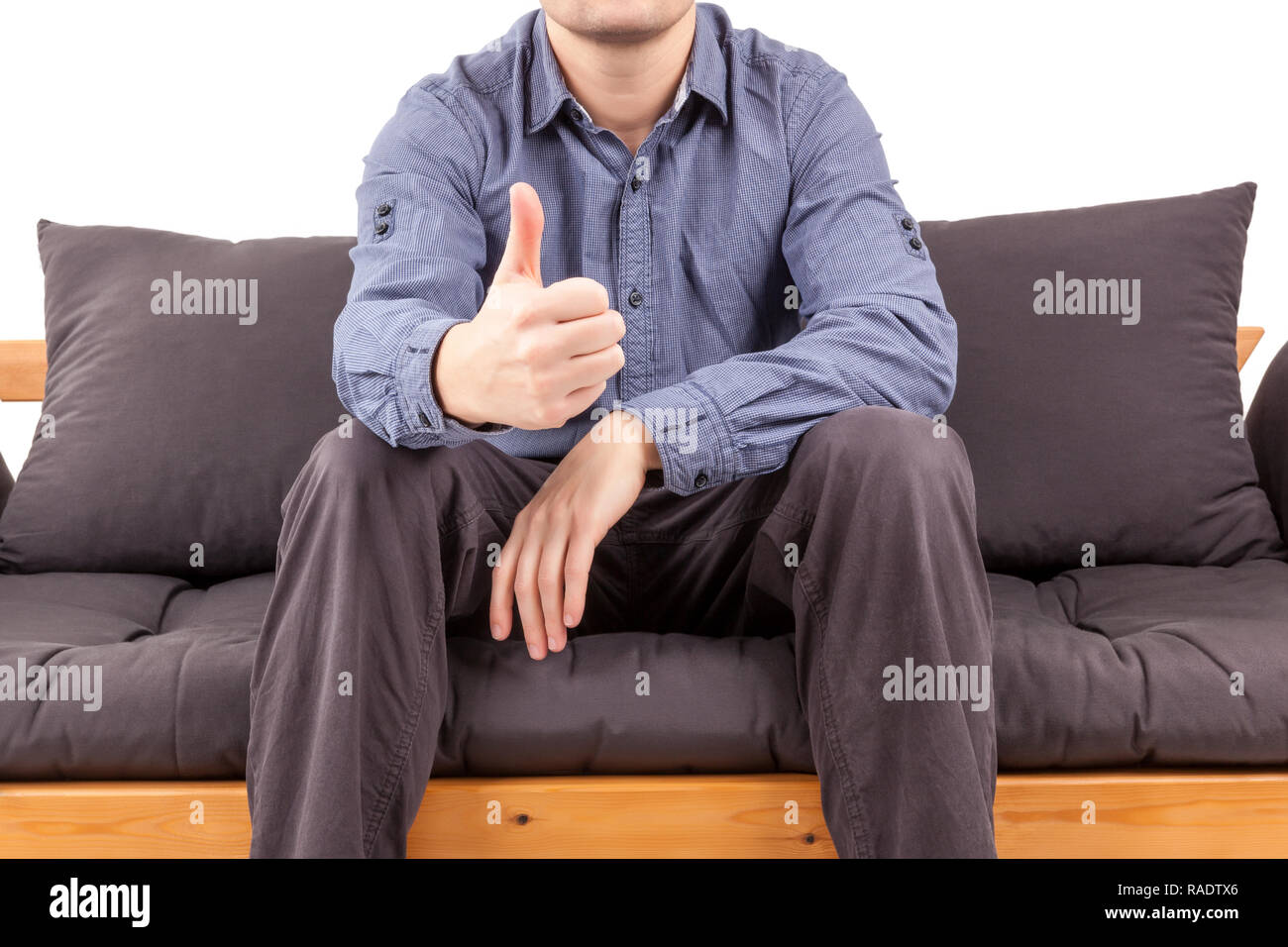 Businessman on sofa showing thumbs up. Mentor and leadership concept. - Stock Image