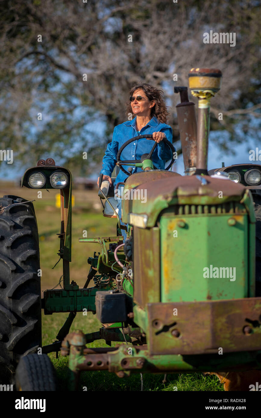 Tammy Higgins, a multi-generational Native American rancher who raises 80 head of cattle on her farm sits on her 1964 John Deere 2510 tractor in of Okfuskee County, Oklahoma. - Stock Image