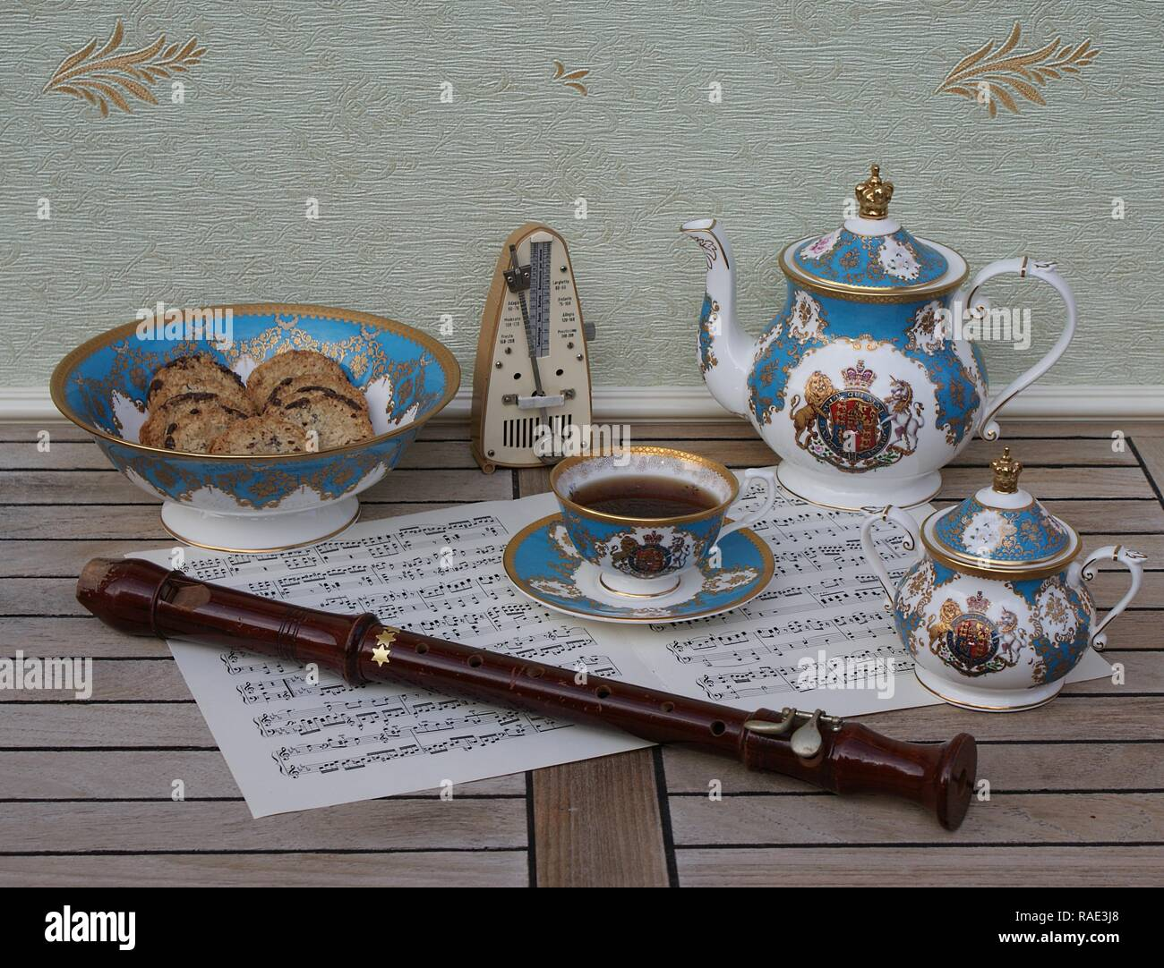 English teacup with saucer, teapot, sugar bowl and a cake bowl with cookies, metronome for music and a block flute on a sheet of music - Stock Image